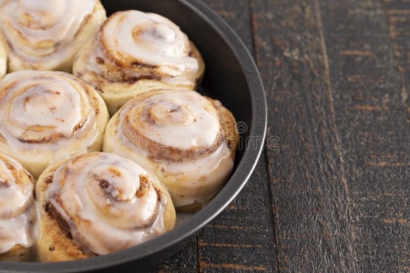 Cinnamon Rolls in a Pan on a Rustic Wooden Table. Frosted Cinnamon Rolls in a Pan on a Rustic Wooden Table stock images