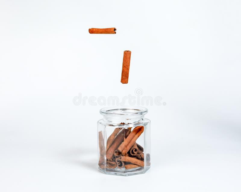 Cinnamon spice dropping in glass ja royalty free stock images