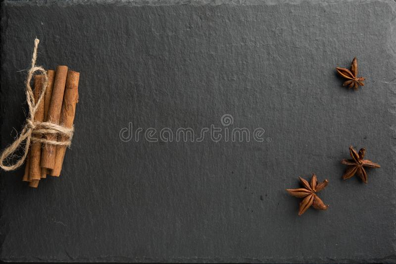 Cinnamon stick and star anise spice. Bunch of cinnamon stick and star anise spice on dark slate background stock image