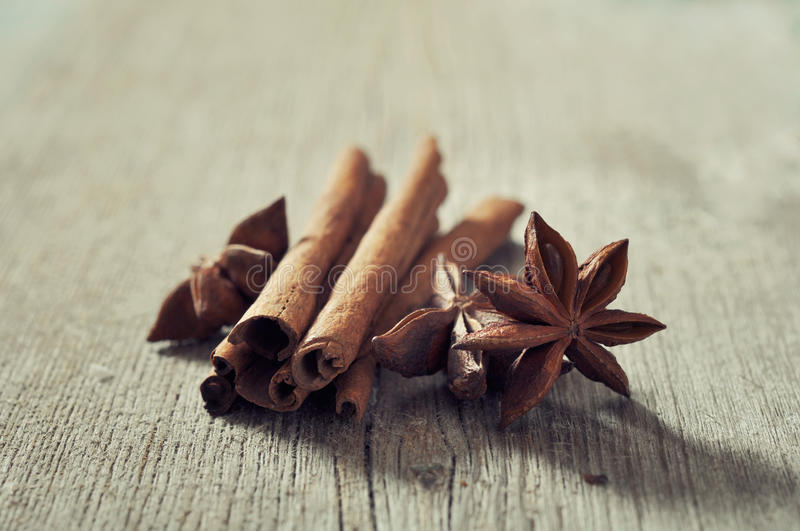 Cinnamon sticks with anis. Stars closeup on wooden background stock image