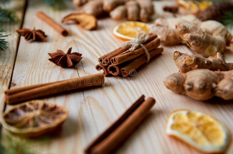 Cinnamon sticks with anise stars, ginger, dried oranges on the wooden background decorated with Christmas tree branches stock photography