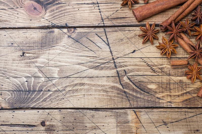 Cinnamon sticks and anise stars on wooden background. Copy space. Top view stock photography