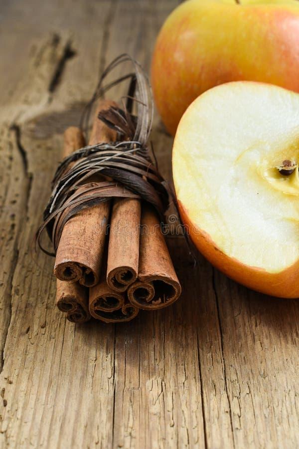 cinnamon sticks with apple on wooden table stock photos