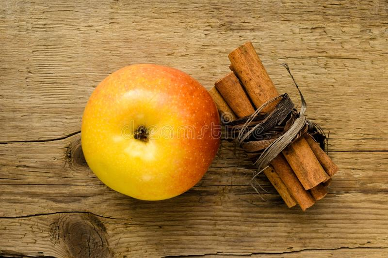 Cinnamon sticks and apple on wooden table ingredient royalty free stock photography