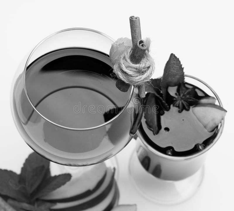 Cinnamon sticks, ginger, mint leaves, apple slices and anise in glass. Glass of red wine on white. Fresh and mulled wine stock image