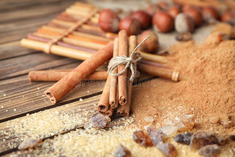 Cinnamon sticks, powder and sugar on wooden background, closeup stock photo