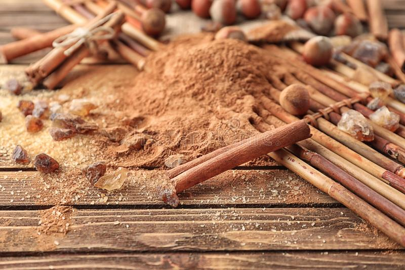 Cinnamon sticks, powder and sugar on wooden background, closeup royalty free stock photo