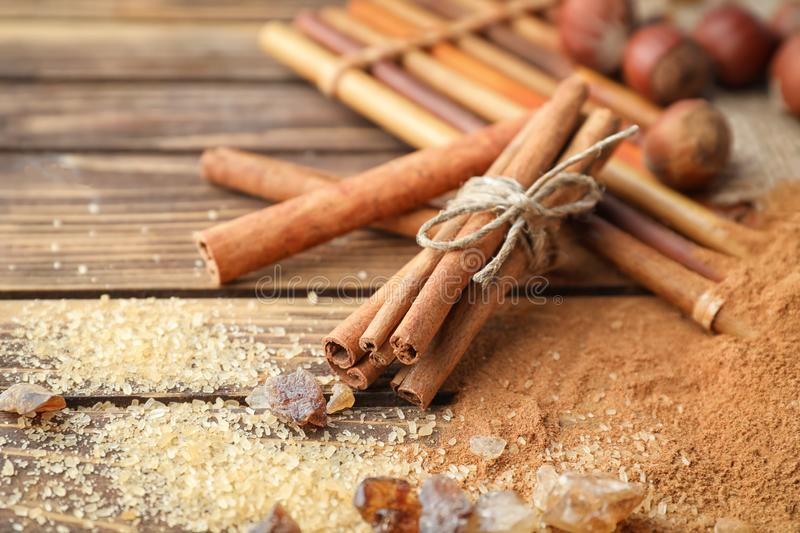 Cinnamon sticks, powder and sugar on wooden background, closeup royalty free stock photography