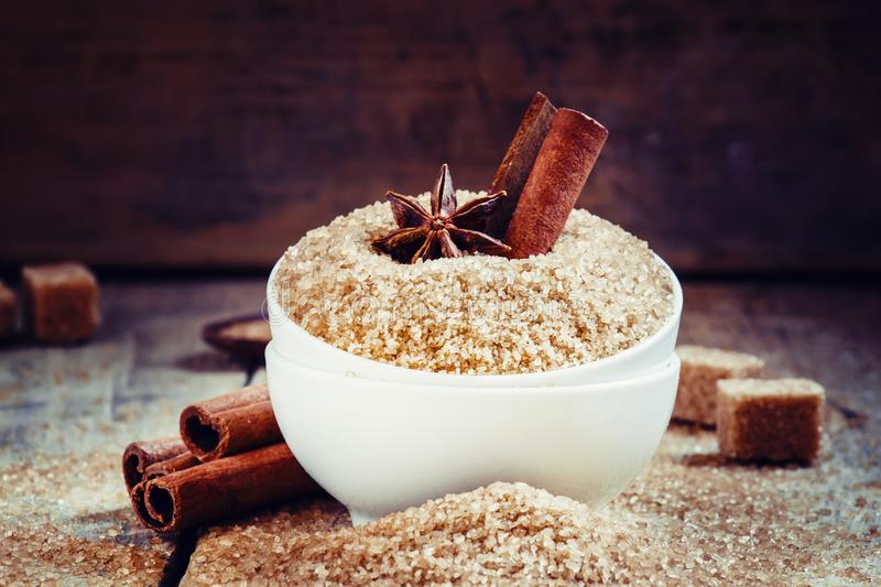 Cinnamon sticks, star anise in a white mask with brown cane sugar on the old wooden background, selective focus stock photography