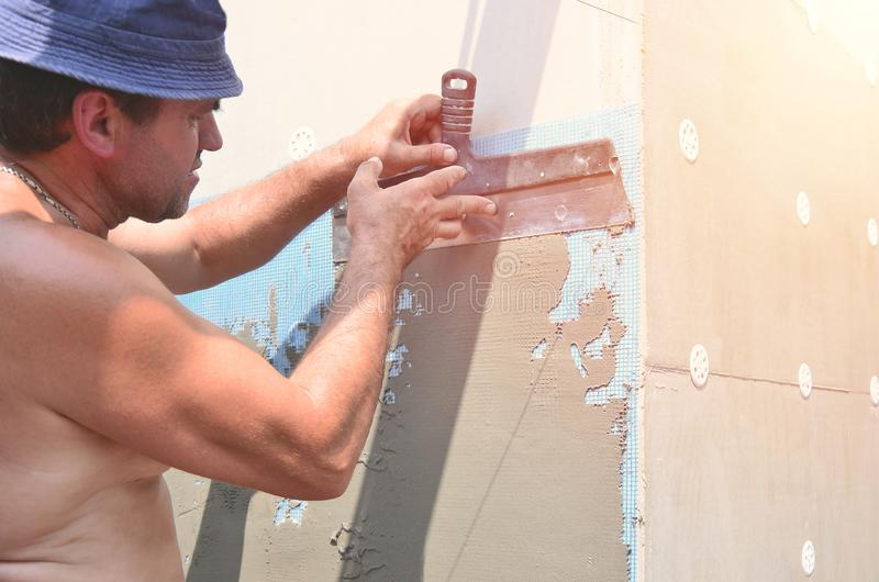 Cinqüênta anos de trabalhador manual idoso com parede que emplastra ferramentas que renova a casa Estucador que renova paredes e  fotos de stock royalty free