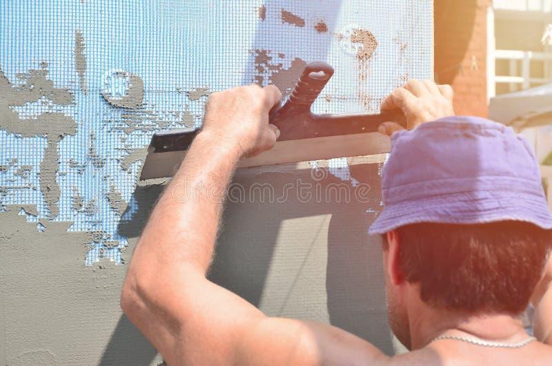 Cinqüênta anos de trabalhador manual idoso com parede que emplastra ferramentas que renova a casa Estucador que renova paredes e  foto de stock
