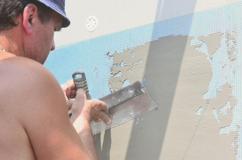 Cinqüênta anos de trabalhador manual idoso com parede que emplastra ferramentas que renova a casa Estucador que renova paredes e  imagem de stock
