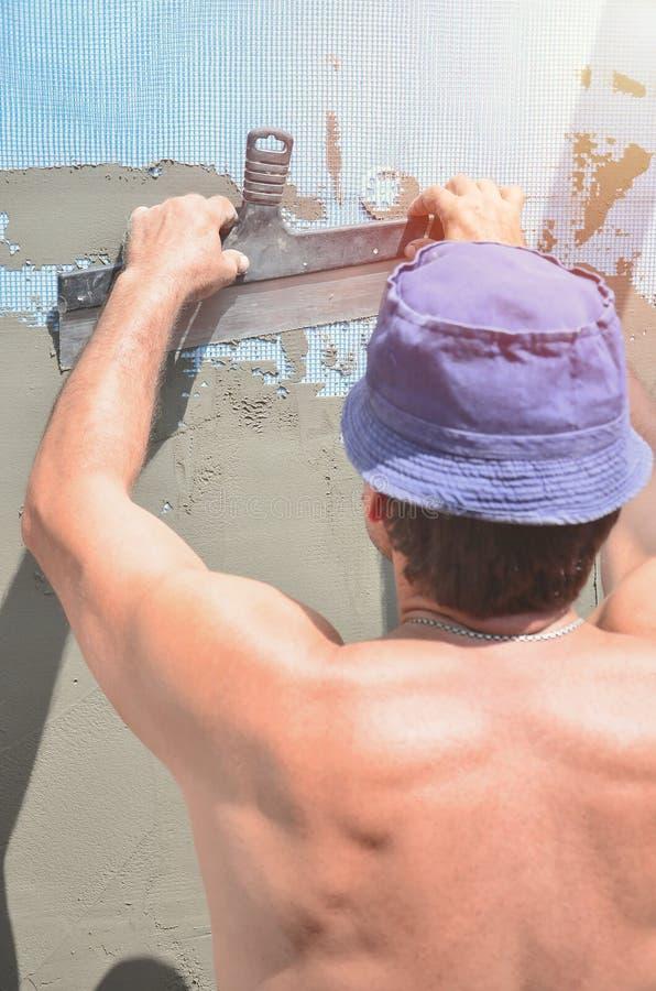 Cinqüênta anos de trabalhador manual idoso com parede que emplastra ferramentas que renova a casa Estucador que renova paredes e  fotografia de stock