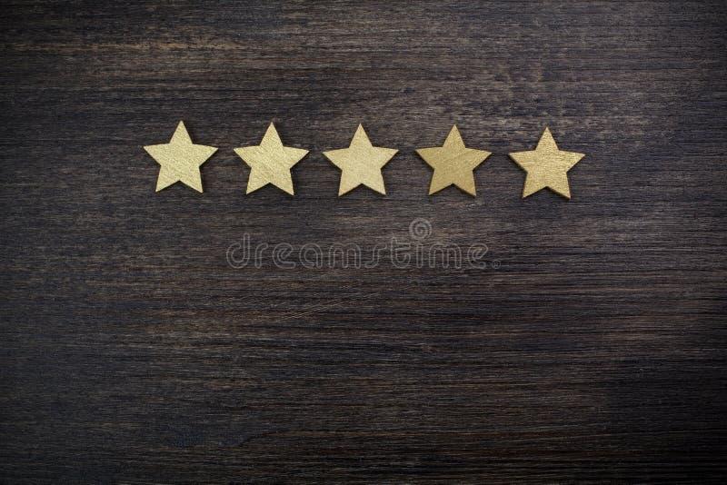 Cinq étoiles d'or sur le fond en bois, concept de évaluation supérieur images stock