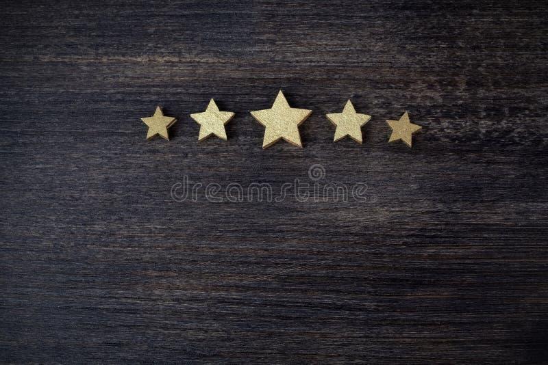 Cinq étoiles d'or sur le fond en bois, concept de évaluation supérieur photographie stock libre de droits