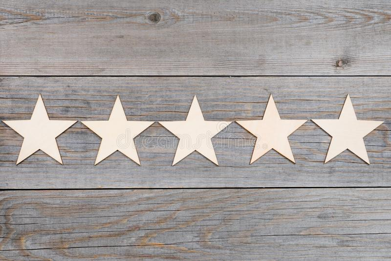 Cinq étoiles dans une rangée sur les planches en bois, concept de évaluation supérieur image libre de droits