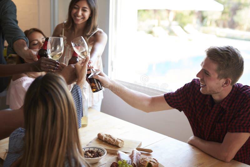 Cinq amis font un pain grillé à un dîner dans la cuisine photos libres de droits