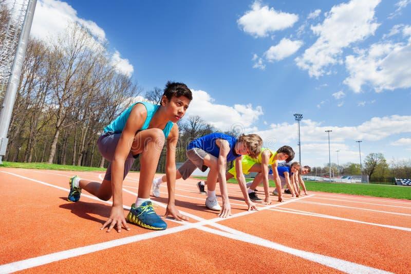 Cinq athlètes adolescents prêts à fonctionner sur un champ de courses image stock