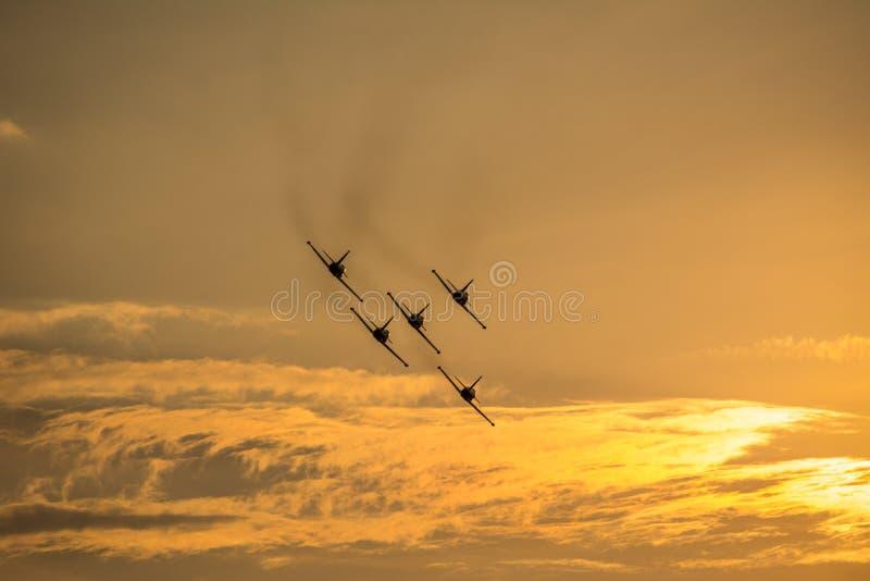 Cinq avions volant au coucher du soleil photographie stock libre de droits