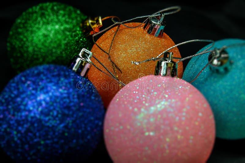 Cinq bals de Noël colorés et de la nouvelle année pour décorer le sapin de Noël se trouvent sur un fond noir photographie stock