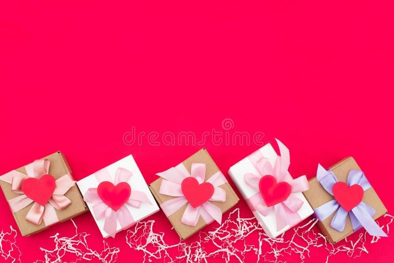 Cinq boîte-cadeau attachés avec le satin ont coloré le ruban sur un fond rouge un coeur rouge images libres de droits