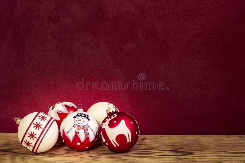 Cinq boules d'arbre de Noël sur un conseil en bois image stock