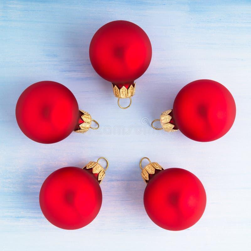 Cinq boules rouges de Noël sur la vue supérieure de fond en bois bleu-clair images stock