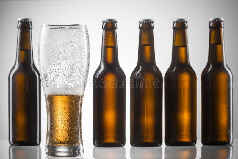 Cinq bouteilles et verre à moitié vide images libres de droits