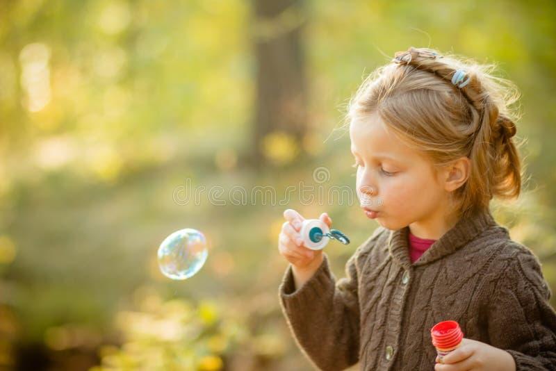 Cinq bulles de savon de soufflement de fille caucasienne d'enfant d'années extérieures au coucher du soleil - enfance insouciant  photos stock