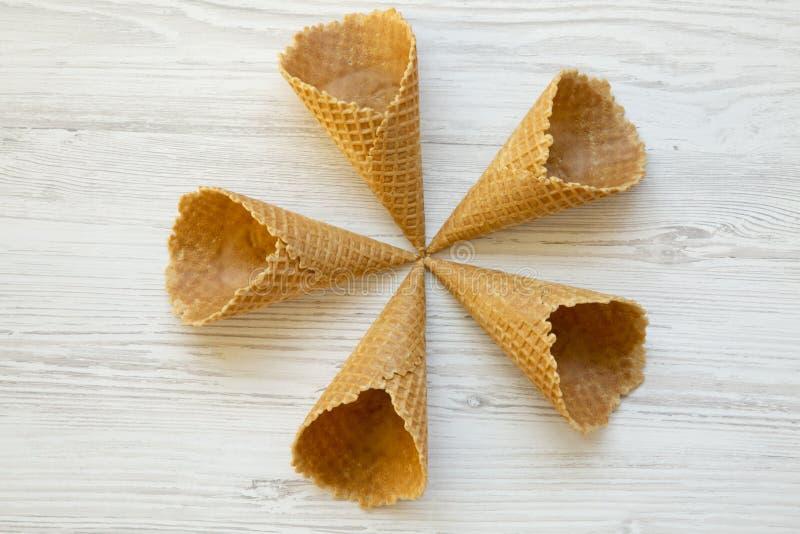 Cinq cônes de gaufre de crème glacée sur un fond en bois blanc, configuration plate D'en haut, photographie stock libre de droits