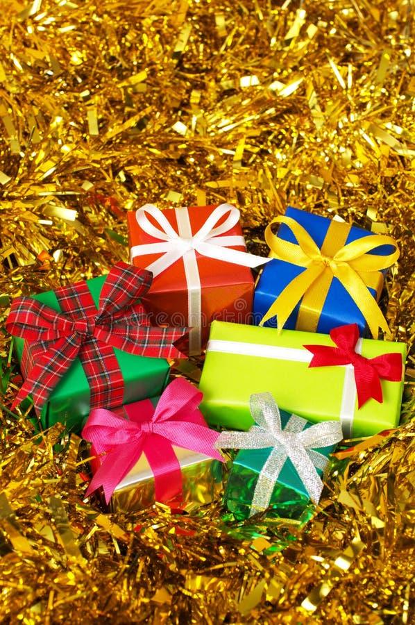 Cinq cadeaux colorés sur la tresse d'or. (verticale) photographie stock