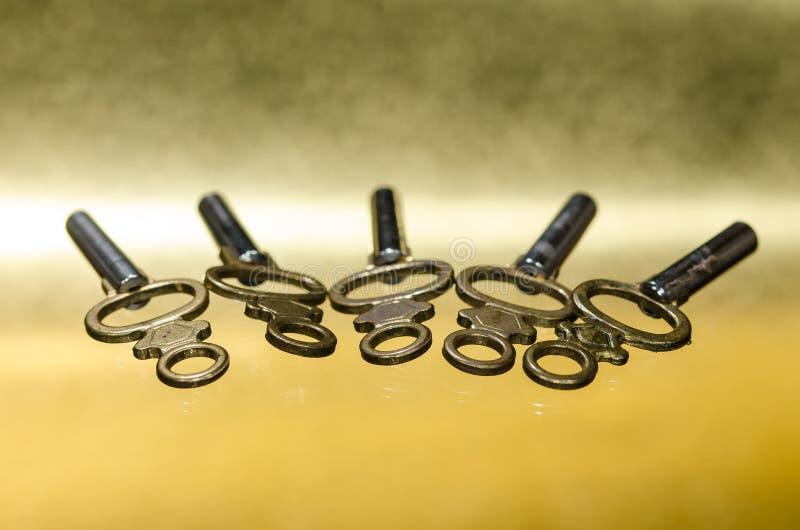 Cinq clés de montre en laiton antiques de poche s'étendant sur la surface d'or images stock