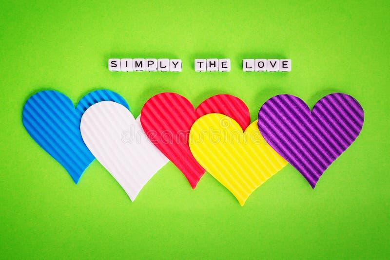 Cinq coeurs multicolores de valentine et l'inscription simplement l'amour fait en cubeson blanc d'alfphabet un fond vert photo libre de droits