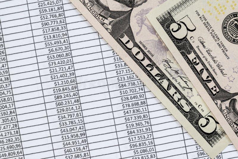 Cinq dollars de billet de banque au-dessus d'une feuille de calcul d'exceler avec I financier photographie stock libre de droits