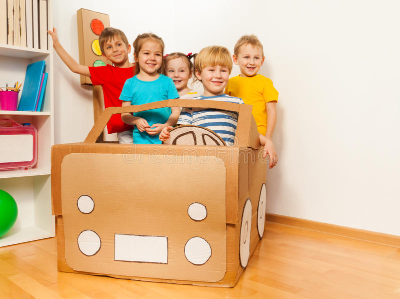 Cinq enfants de sourire conduisant la voiture faite main de carton photos stock