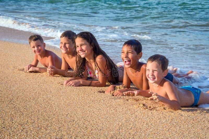 Cinq enfants de sourire se couchant sur la plage photos libres de droits