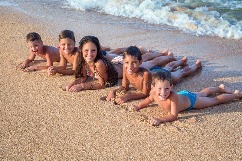Cinq enfants heureux sur la plage images libres de droits