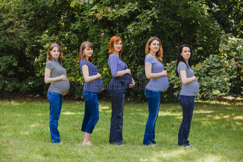 Cinq femmes enceintes dans la même chose vêtx extérieur photo stock