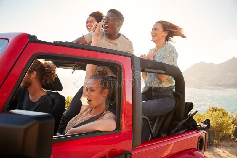 Cinq jeunes amis adultes sur un voyage par la route conduisant dans une jeep à couvercle serti par la mer photo libre de droits