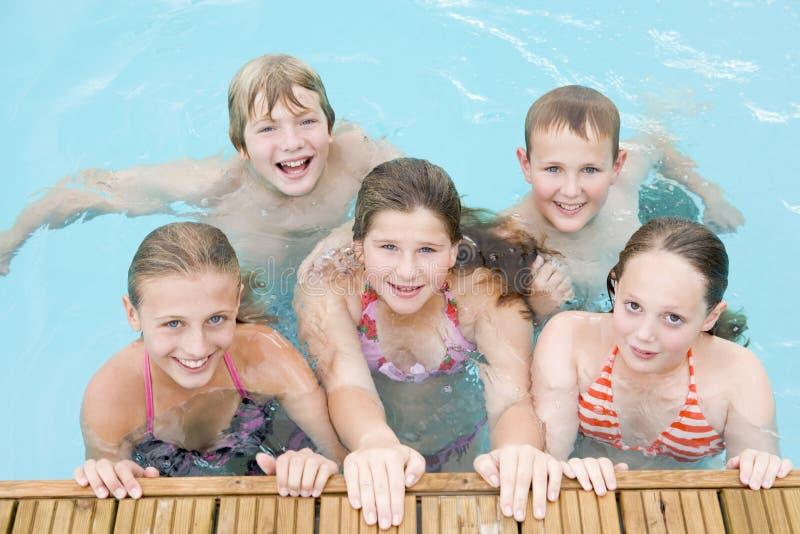 Cinq jeunes amis dans le sourire de piscine photos libres de droits