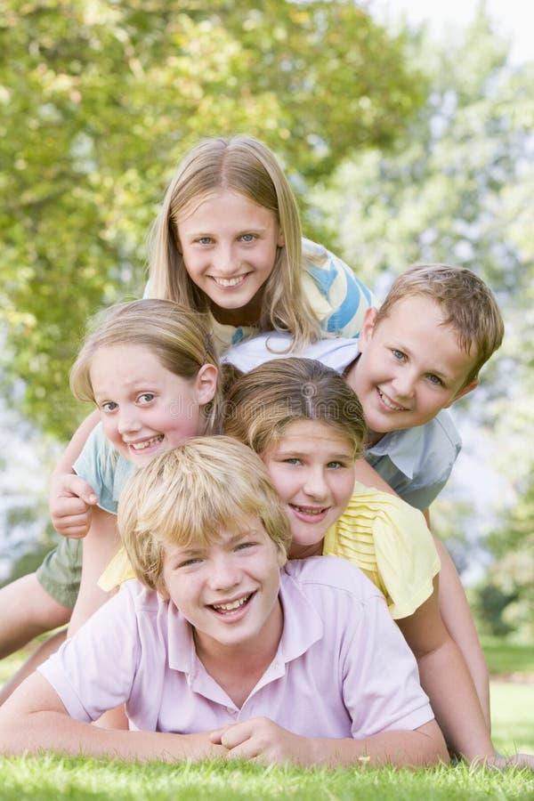 Cinq jeunes amis empilés sur l'un l'autre à l'extérieur photos libres de droits
