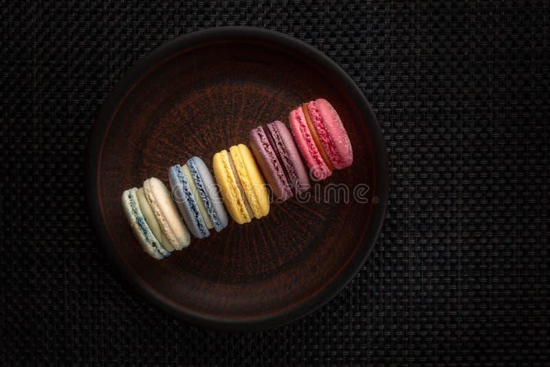 Cinq macarons doux multicolores sur le fond brun de plat et de modèle image libre de droits