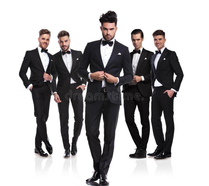 Cinq mariés beaux avec le chef boutonnant le costume dans l'avant image stock
