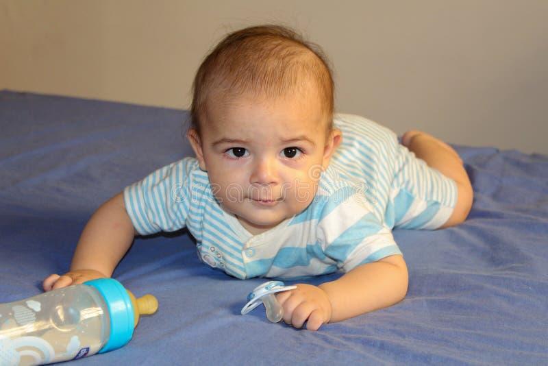 Cinq mois de bébé garçon jouant sur le lit image libre de droits