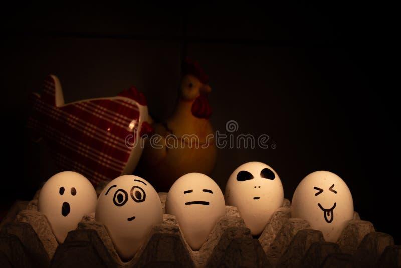 Cinq oeufs avec les visages drôles Ils sont observés plus de par deux poulets hors focale Image conceptuelle images stock