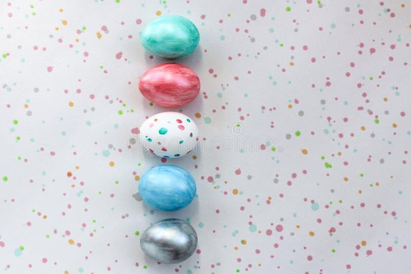 Cinq oeufs colorés se trouvent sur un fond repéré Pâques, oeufs de coloration créatifs indépendamment à la maison pour la décorat photographie stock libre de droits