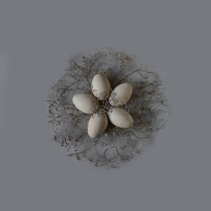 Cinq oeufs de pâques en bois dans un nid sous forme de flover sur un fond gris photos libres de droits
