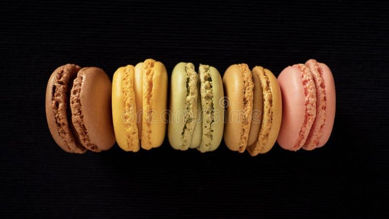 Cinq saveurs et couleurs différentes des macarons ou des macarons français traditionnels, alignées et d'isolement sur le fond fon images stock