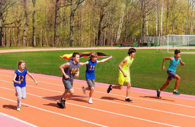 Cinq sprinters adolescents courant avec le drapeau allemand photos libres de droits