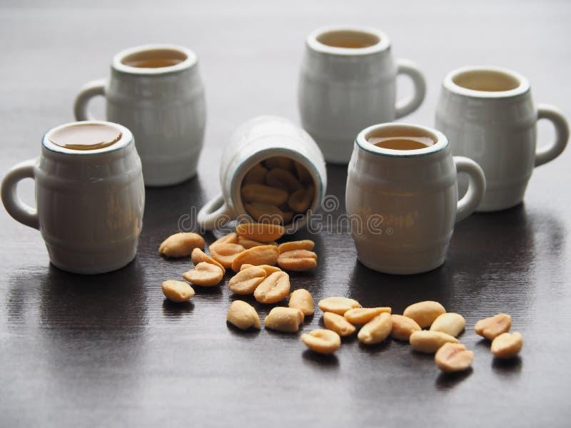 Cinq tasses de bière et une tasse avec les arachides salées images libres de droits